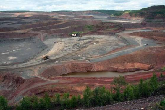 The worlds biggest open pit mine can be found near Hibbing, Minnesota. At its maximum, the area covered by the Hull Rust open pit mine is five miles (8km) long, 2 miles (3,2km) wide and 535 feet (180m) deep. It looks like a man-made Grand Canyon of over 2,000 acres (8,1km²). The first iron ore extractions were made here in 1895. Beginning as a small underground mine, the land eventually became one vast open pit as other mines began to develop and emerge. The center of the actual pit is located where the original town of Hibbing once stood. As the mine grew bigger, the town had to be moved. The move started in 1919 and took two years to complete. 185 houses and 20 businesses were moved a couple of miles to the south. Some of the larger buildings even had to be cut in half before they could be moved. A few remnants of the original town are left near a lookout point at the edge of the mine.